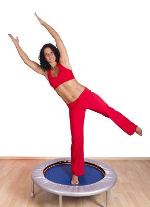 Frau macht Gleichgewichtsübungen auf einem Fitnesstrampolin